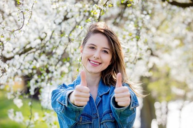 Девушка в джинсовой куртке стоит возле цветущего дерева и показывает знак ок рукой Premium Фотографии