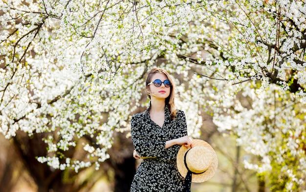 Молодая девушка в солнцезащитных очках и шляпе возле цветущего дерева Premium Фотографии