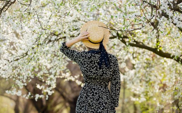 Молодая девушка в шляпе возле цветущего дерева Premium Фотографии