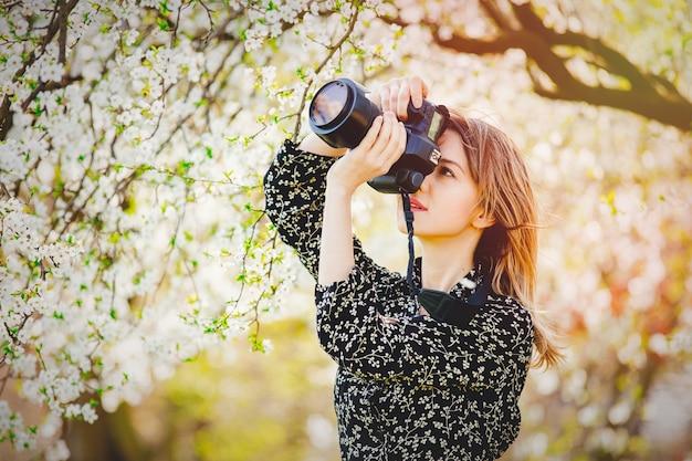 Девушка с профессиональным фотоаппаратом делает изображение цветущего дерева Premium Фотографии