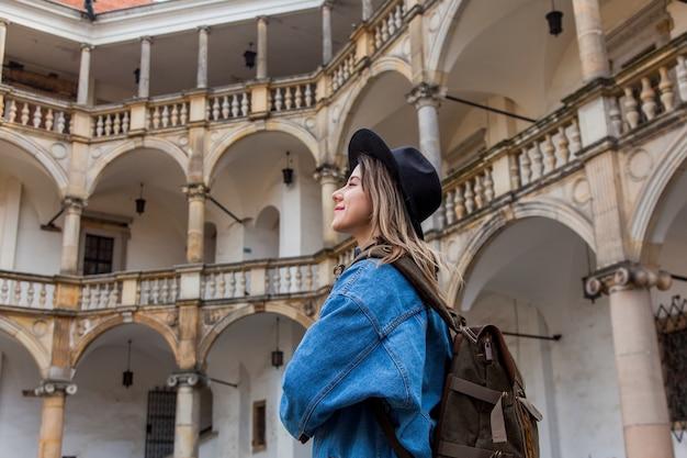古いお城のバックパックと帽子とデニムのジャケットの若い女性 Premium写真