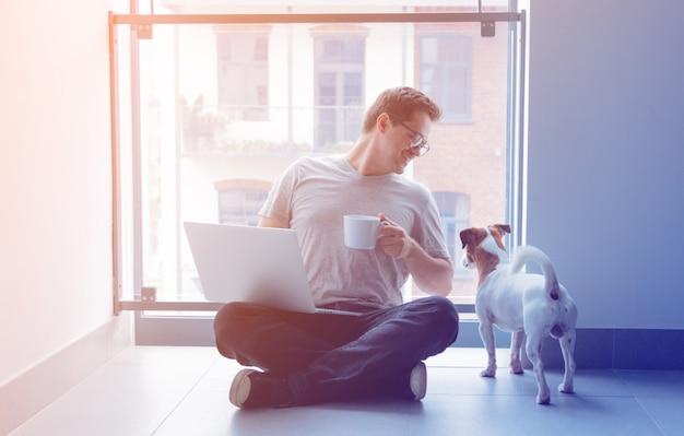 ラップトップコンピューターと一杯のコーヒーを使用してフリーランサー男 Premium写真
