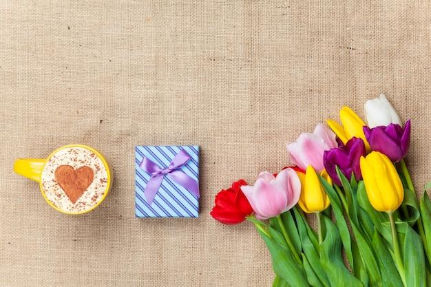Капучино и подарочная коробка возле цветов Premium Фотографии