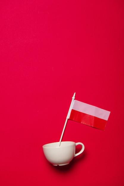 赤の背景に白いカップとポーランドの国旗 Premium写真