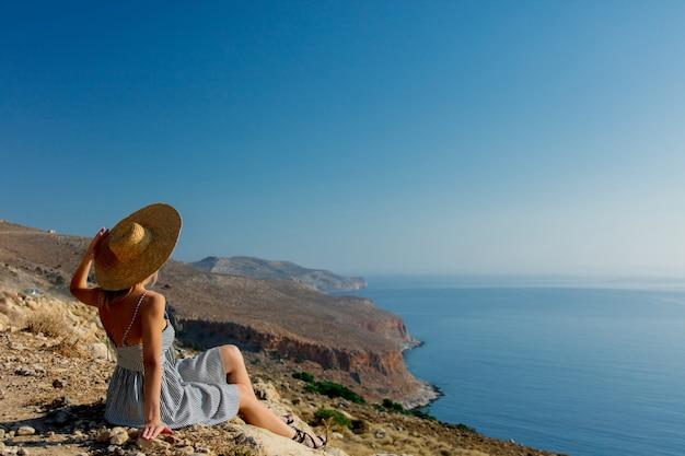 帽子と海の海岸線とドレスの女の子 Premium写真