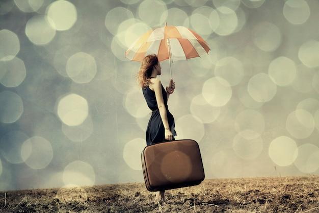 Рыжая девушка с зонтиком и чемоданом на ветреном поле Premium Фотографии