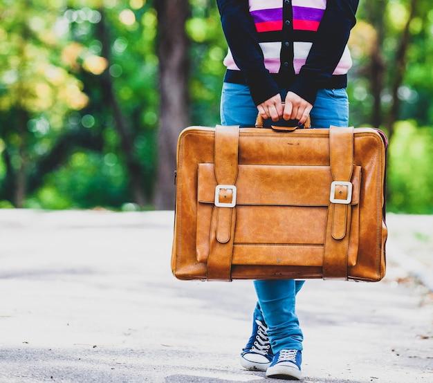 公園でスーツケースを持つ若い十代のガート Premium写真