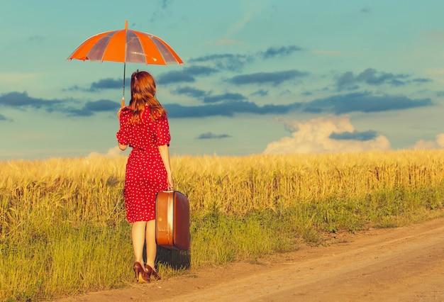 傘と屋外でスーツケースの赤毛の女の子 Premium写真