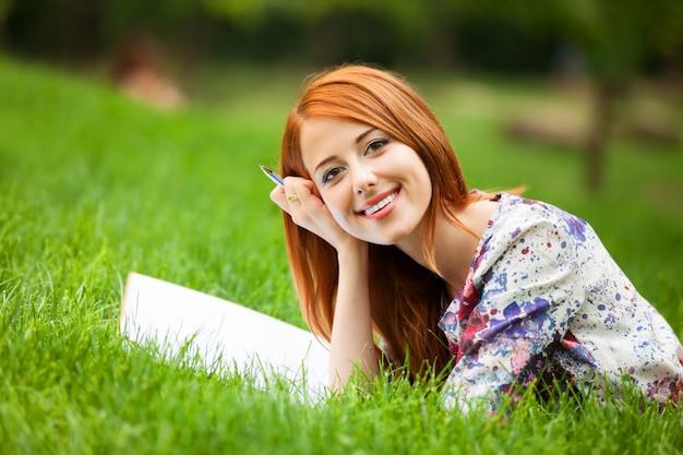 屋外でメモを持つ美しい若い女性 Premium写真