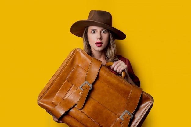 Молодая женщина в шляпе с чемоданом Premium Фотографии