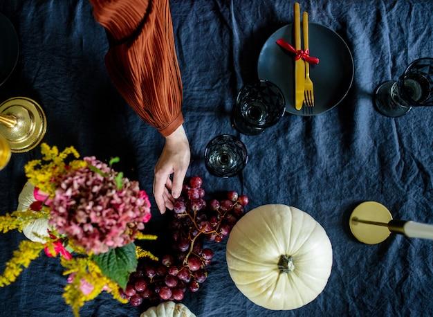 Женщина накрывает на стол в канун осенних каникул Premium Фотографии