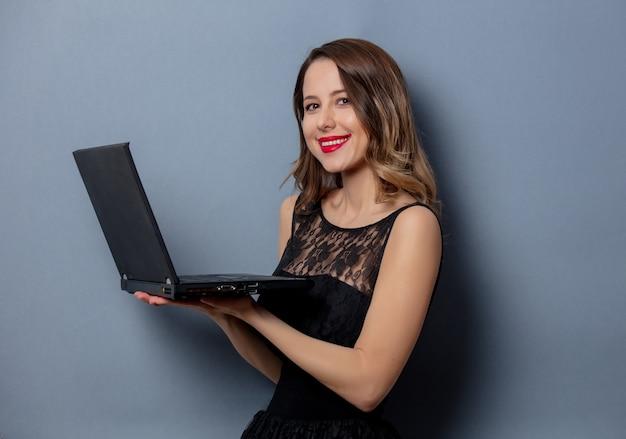 Молодая женщина в черном платье с ноутбуком на серой стене Premium Фотографии