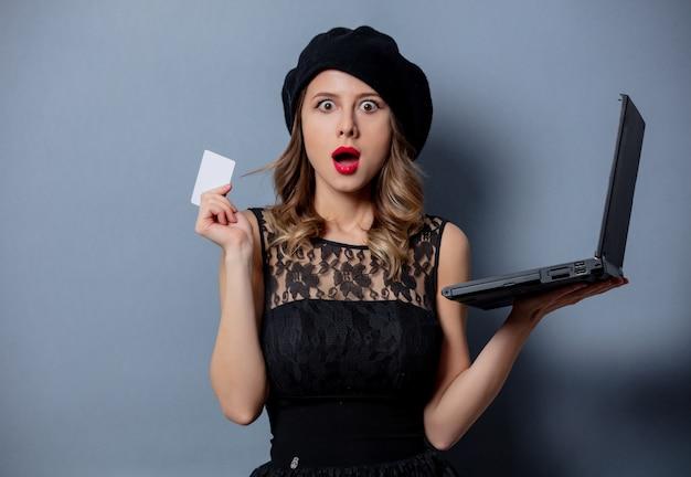 ノートブックと灰色の壁にカードと黒のドレスの若い女性 Premium写真