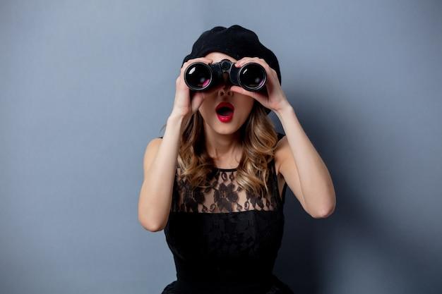 Молодая женщина в черном платье с биноклем на серой стене Premium Фотографии