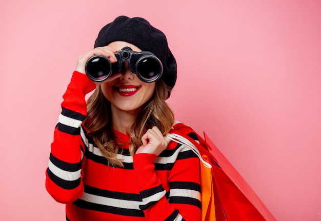 Молодая женщина с биноклем и сумок на розовой стене Premium Фотографии