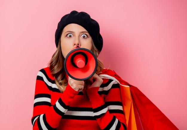 Молодая женщина с хозяйственными сумками и громкоговорителем на розовой стене Premium Фотографии