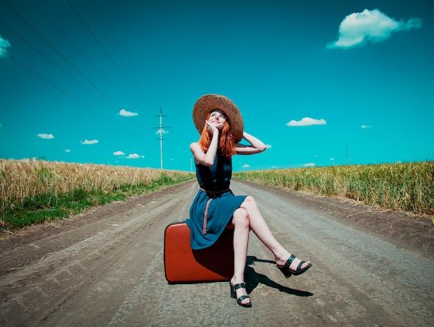 青いドレスと田舎道でスーツケースと帽子の少女 Premium写真
