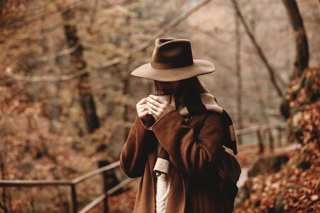秋の公園でコーヒーのカップを持つ若い女性 Premium写真