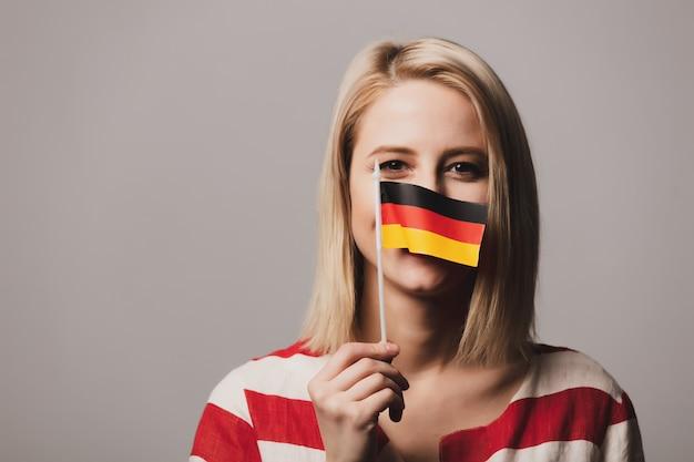 Красивая девушка держит немецкий флаг Premium Фотографии