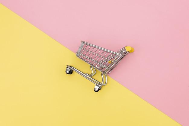 ピンクと黄色の背景に金属製のショッピングカート。 Premium写真