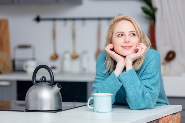 Блондинка с чашкой кофе на кухне Premium Фотографии