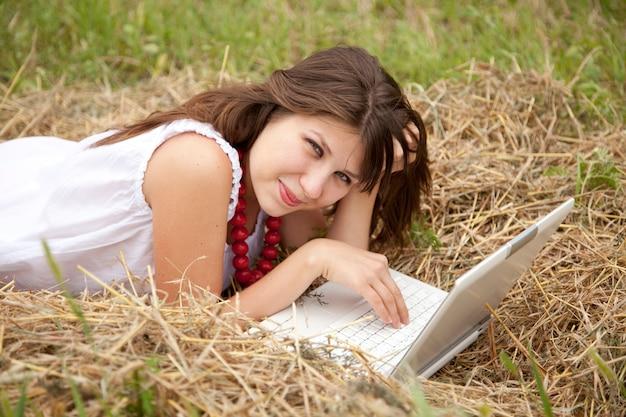 フィールドで横になっているノートブックと若者のファッションの女の子 Premium写真