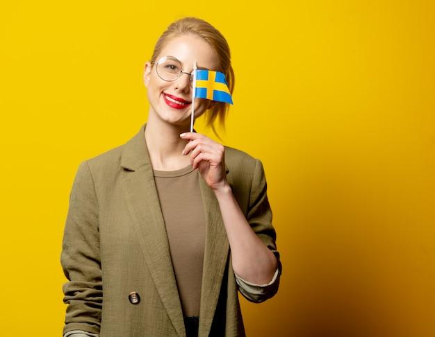 Стильная блондинка в куртке со шведским флагом на желтом Premium Фотографии
