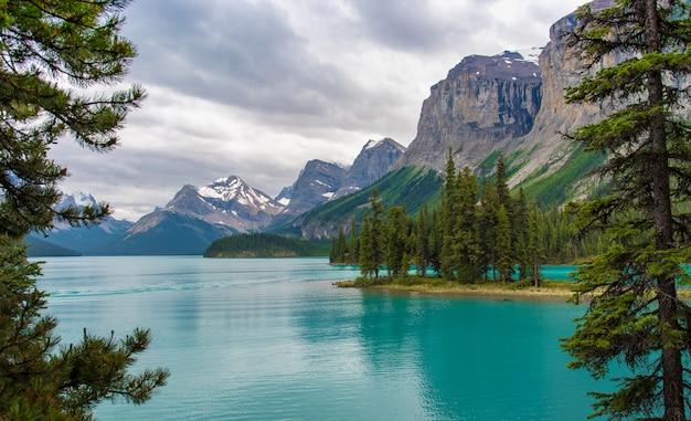 背景に、アルバータ州、カナダの大きな山とスピリット島のカナダの森林風景。 Premium写真