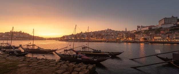 Панорамный городской пейзаж порту в закат с рекой на фронте и винный корабль на переднем плане и город порту в фоновом режиме, португалия Premium Фотографии