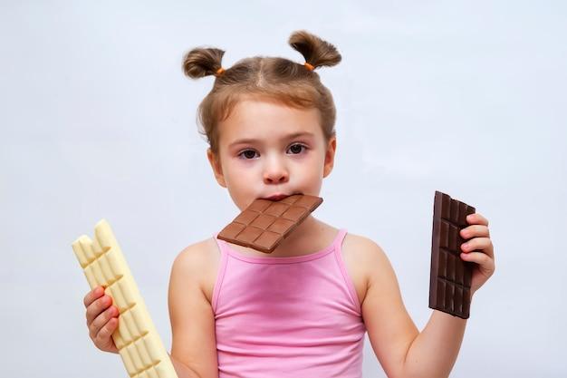 Удивленная смешная маленькая девочка держа шоколад и смотря. Premium Фотографии
