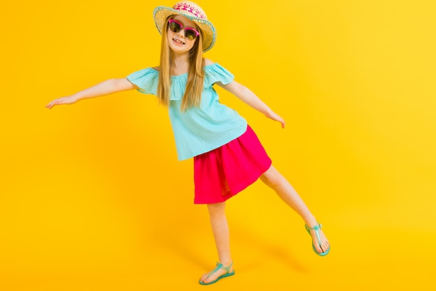 帽子、サングラス、夏のドレス、サンダルで美しい少女の肖像画。 Premium写真