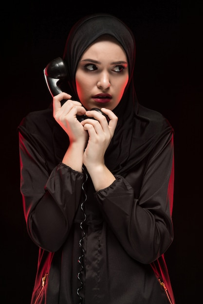Портрет красивой серьезной испуганной молодой мусульманки в черном хиджабе, шепчущей с просьбой о помощи на черной футболке Premium Фотографии