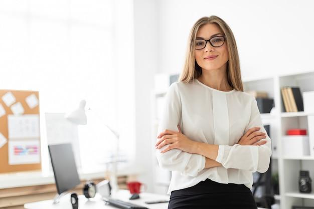 若い女の子がオフィスのテーブルにもたれて立っています。 Premium写真