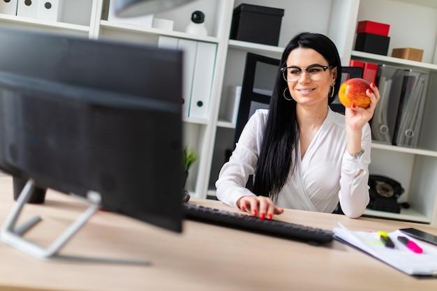 若い女の子がコンピューターの机に座って、彼女の手にリンゴを握り、キーボードに印刷します Premium写真