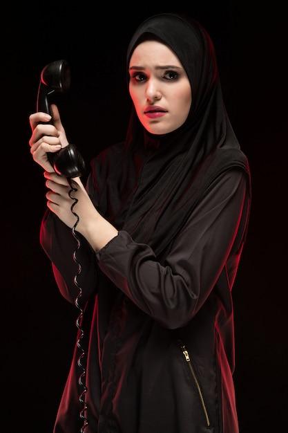 Портрет красивой серьезной испуганной молодой мусульманки в черном хиджабе, зовущей на помощь на черном Premium Фотографии