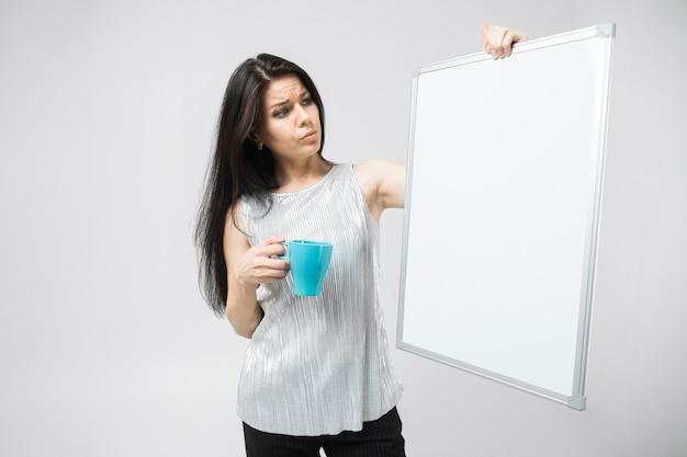 Портрет брюнет улыбается женщина в блузке, держа чашку и доску Premium Фотографии