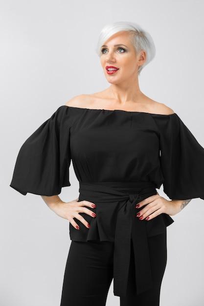 Взрослый красивая улыбчивая модная деловая женщина в свободной одежде поссевает на сером Premium Фотографии