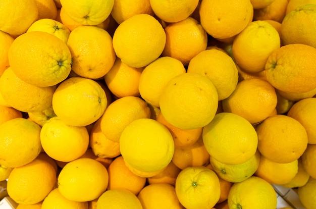 Ярко-желтые лимоны в деревянных коробках на фермерском рынке или в продуктовом магазине Premium Фотографии