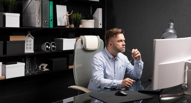コンピューターのデスクでオフィスに座っているとメガネの彼の口の束縛を保持しているビジネスの男性 Premium写真