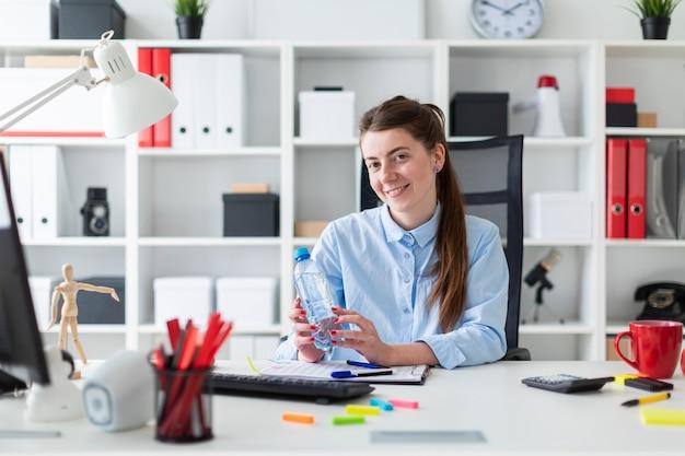 Молодая девушка сидит за столом в офисе и держит бутылку воды в руке. Premium Фотографии
