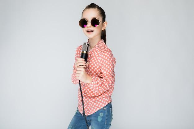 オレンジ色のシャツ、メガネ、グレーにブルージーンズの女の子。 Premium写真
