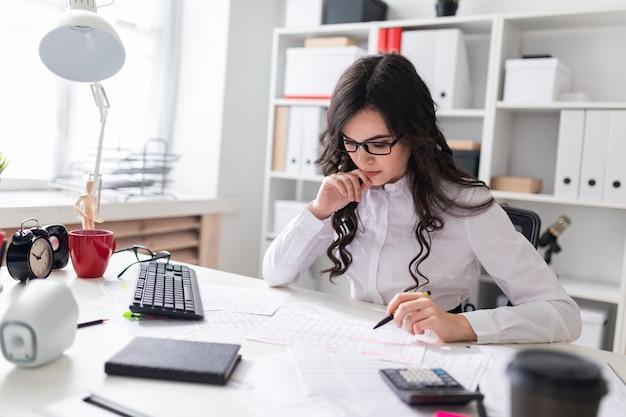 若い女の子がオフィスのテーブルに座って、彼女の手にペンを持って、書類を見ます。 Premium写真