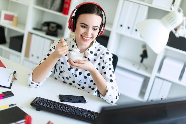 オフィスの机にヘッドフォンで座っている、ヨーグルトを食べるとモニターを見て美しい少女。 Premium写真