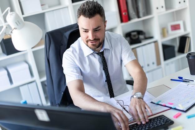 男はオフィスのテーブルに座って文書とコンピューターを操作しています。 Premium写真
