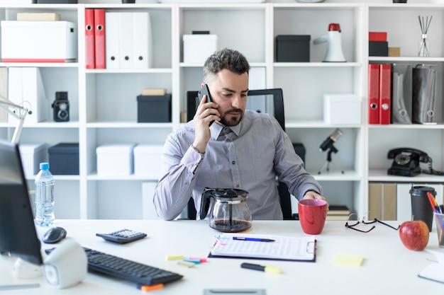 事務所の若い男がテーブルに座って、電話で話して、赤いカップを手に持っています。 Premium写真