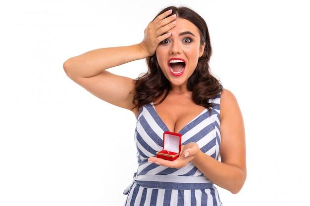 楽しい笑顔、平らな歯、赤い口紅、長いウェーブのかかった栗の髪、美しいメイク、胸の谷間とストライプの白と青のドレスの少女は、彼女の手に赤いリングボックスを保持しています Premium写真