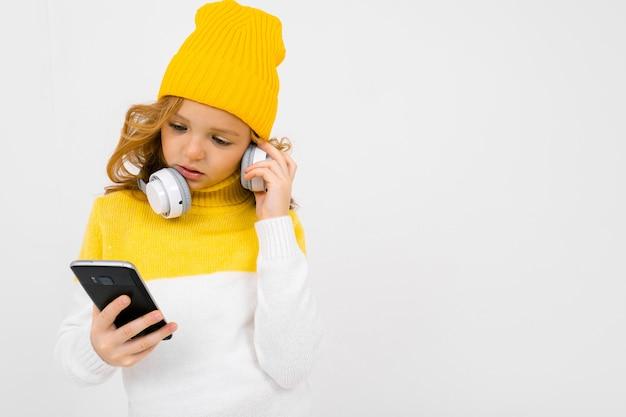Европейская привлекательная девушка читает сообщения на смартфоне с наушниками на ее шее, изолированных на белом фоне Premium Фотографии