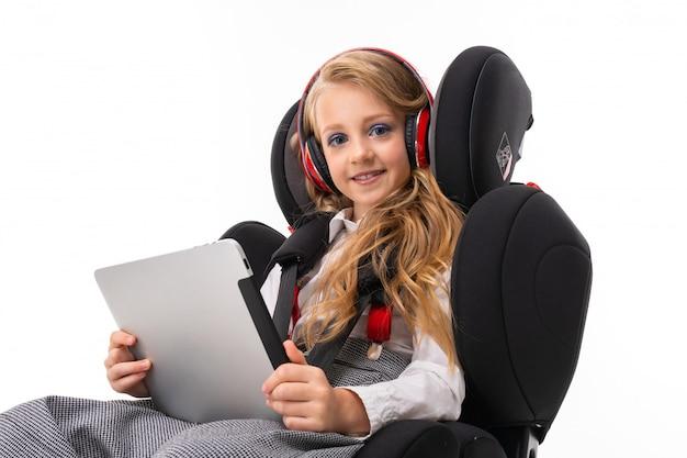 Маленькая девочка с макияжем и длинными светлыми волосами сидит в детском автомобильном кресле с планшетом, наушниками, слушает музыку и общается с друзьями Premium Фотографии