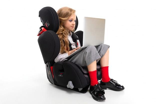 Маленькая девочка с макияжем и длинными светлыми волосами сидит в детском автомобильном кресле с ноутбуком, наушниками, слушает музыку и общается с друзьями Premium Фотографии
