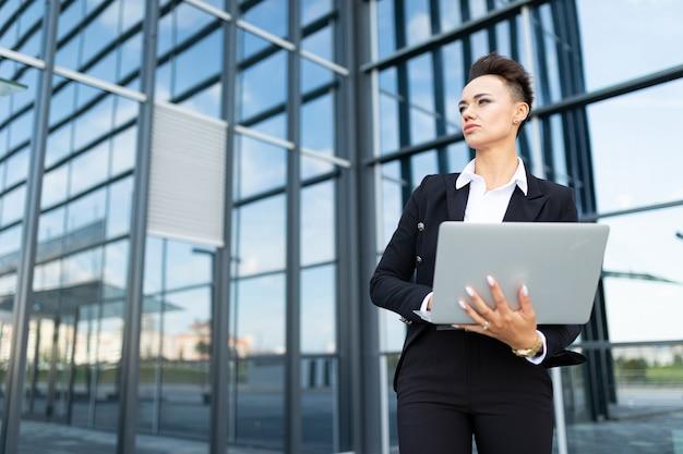 Молодая успешная бизнес-леди с ноутбуком Premium Фотографии